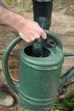 Filling up the watering-can. Frontal portrait view of a hand filling up the watering can at a pump well Royalty Free Stock Photography