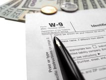 filling the w-9 tax form by black ink pen, money Royalty Free Stock Photography