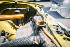 Filling water coolant. Closeup old car radiator with open cap filling water coolant, Check Your Car Before a Road Trip Concept Stock Photography
