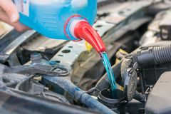 Filling the water tank with antifreeze in the engine compartment of a car royalty free stock image