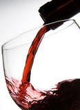 Filling wine glass. Red wine pouring into wineglass isolated on white background Stock Image