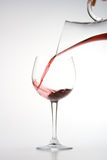 Filling wineglass from decanter. Red wine pouring from decanter into wineglass isolated on white background Royalty Free Stock Images