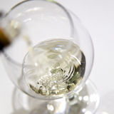 Filling a wineglass with white wine Royalty Free Stock Images