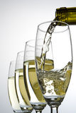 Filling wineglasses with wine. White wine pouring into one of four glasses Royalty Free Stock Images