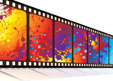 Film along rainbow. Film in perspective with bright colored rainbow ink splat design Royalty Free Stock Photo