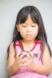Film asiatico sveglio dell'orologio della ragazza sul cellulare Immagini Stock Libere da Diritti