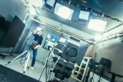 Film camera in broadcasting studio, spotlights and equipment, cameraman in the blurry background. Lens of a film camera in an television broadcasting studio royalty free stock images