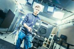 Film camera in broadcasting studio, spotlights and equipment, cameraman in the blurry background. Lens of a film camera in an television broadcasting studio stock image