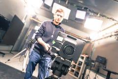 Film camera in broadcasting studio, spotlights and equipment, cameraman in the blurry background. Lens of a film camera in an television broadcasting studio stock photos