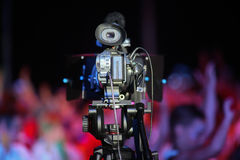 Film camera in front of a cheering crowd Royalty Free Stock Image