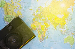 Film camera lay on world map Royalty Free Stock Image
