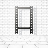 Film or camera strip with shadow near white brick wall.  Royalty Free Stock Photos