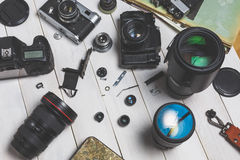 Film cameras, components, digital cameras, and lenses on wooden white background technology development concept Stock Image