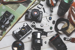 Film cameras, components, digital cameras, and lenses on wooden white background technology development concept Stock Photography