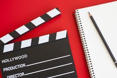 Film clapper on red background. Film clapper and pen notepad on red background