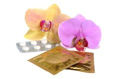 Film-coated tablets and condoms with two orchid flowers isolated Stock Photos