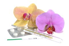 Film-coated tablets, mercury thermometer, ovulation test, orchid flowers Royalty Free Stock Image