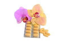 Film-coated tablets with two orchid flowers isolated Royalty Free Stock Images