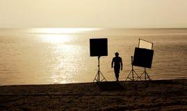 Film crew on a beach. Film crew setting up scene on a beach Stock Photo