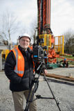 Film crew at work. A documentary filmmaker poses with his camera on location at a drilling rig Stock Image