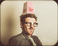 Film critic nerd. Retro photograph of a funny movie critic wearing popcorn knowledge hat. Film nerds Royalty Free Stock Image