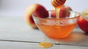 Film de l'égoutture de miel Pommes sur la table en bois Nourriture traditionnelle de célébration pendant la nouvelle année juive  clips vidéos