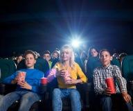 Film de la jeunesse et casse-croûte de observation de consommation dans le théâtre de film Photo stock
