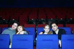 Film de montre des quatre jeunes dans le théâtre de cinéma. Photographie stock libre de droits