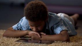 Film de observation de comprimé de garçon seul se trouvant sur le plancher à la maison, manque de communication image libre de droits