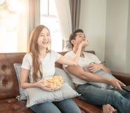 Film de observation de couples asiatiques se reposant sur un sofa à la maison gai et le maïs éclaté de prise à ami Photo stock