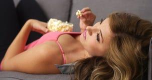 Film de observation de jolie fille et maïs éclaté de consommation Photo libre de droits