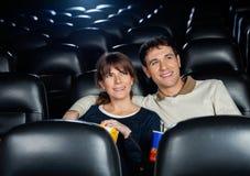 Film de observation de sourire de couples dans le théâtre Photo stock
