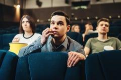 Film de observation effrayé d'homme dans le cinéma image libre de droits