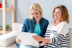 Film de observation heureux de mère et de fille sur l'ordinateur portable image libre de droits
