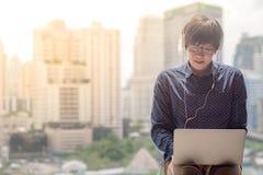 Film de observation de jeune homme asiatique à partir d'ordinateur portable photos libres de droits