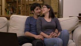 Film de observation de jeunes couples affectueux attrayants sur l'ordinateur portable à la maison dans le salon sur un divan blan banque de vidéos