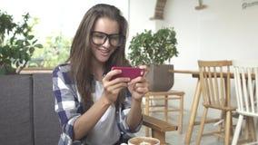 Film dell'orologio della giovane donna sullo smartphone Fotografie Stock Libere da Diritti