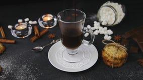 Film di cioccolata calda di versamento con le caramelle gommosa e molle in vetro Bello fondo con le candele, illicium, biscotti c video d archivio