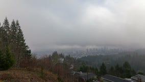 Film di lasso di tempo delle nuvole commoventi e della nebbia bassa sopra la città di Portland nell'Oregon un primo mattino 1080p video d archivio