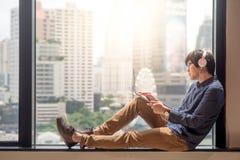 Film di sorveglianza del giovane uomo asiatico dal computer portatile Fotografia Stock