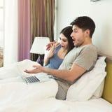 Film di sorveglianza delle coppie felici sul computer portatile a letto fotografie stock libere da diritti
