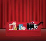 Film di vetro a distanza della scatola 3d di film su DVD della bevanda del popcorn su un sofà rosso con il backgrond rosso della  Fotografie Stock Libere da Diritti