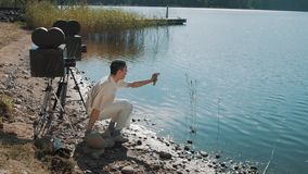 Film director in hair net eat grapes from speaker on lake shore with two camera stock video footage