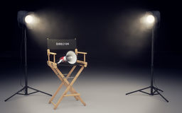 Film director`s chair with megaphone and spotlights. 3D renderin. Film director`s chair with megaphone and spotlights shining. 3D rendering Royalty Free Stock Photo