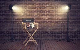 Film director`s chair with megaphone and spotlights. 3D renderin. Film director`s chair with megaphone and spotlights shining. 3D rendering vector illustration