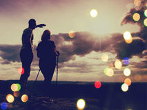 Film effect.  Couple enjoying marvellous moments during sunset . Young pair of hikers on the peak Royalty Free Stock Image