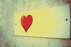 Film effect, film grain. a small white plaque on the wall of pressed plywood. a beautiful red heart with black edging, Billboard. Film effect, film grain. a royalty free stock images