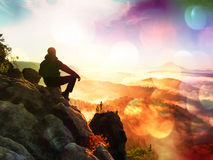 Film effect.Hiker man take a rest on mountain peak. Man lay on summit, bellow autumn valley. Bright morning Sun Stock Images