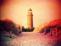 Film effect. Historical lighthouse. Shinning lighthouse,  dunes and pine tree. Tower illuminated with strong warning light,. Film grain effect. Historical Stock Photo