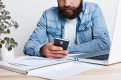 A film effect. Portrait of bearded man in jean shirt hoding smartphone in his hand while working with documents in office with cos. Y interior. Cropped portrait Royalty Free Stock Images